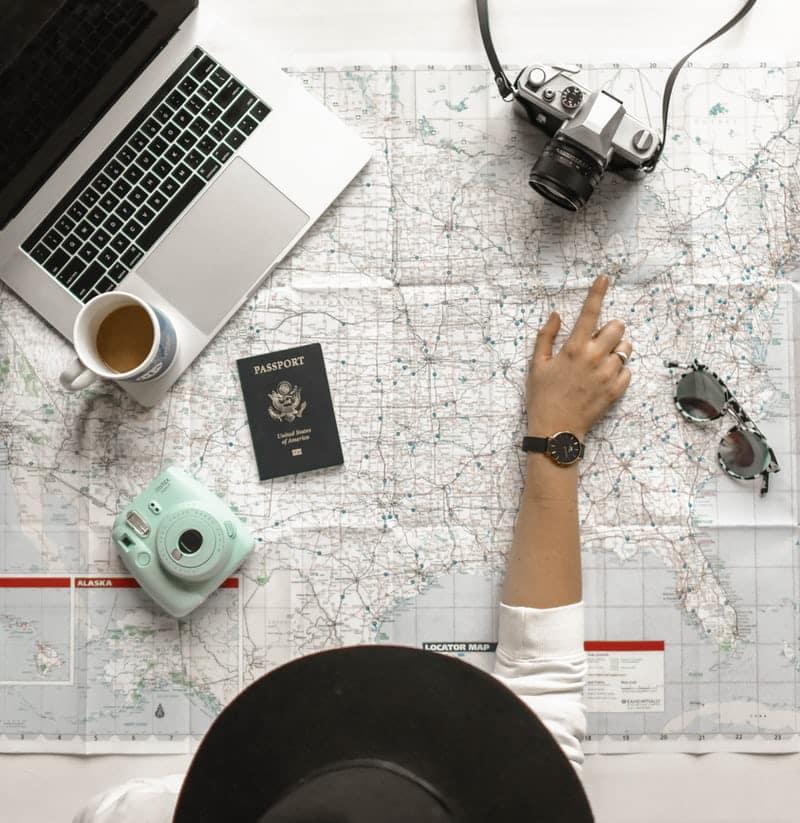 de wereldkaart met daarop een laptop, een mok koffie, 2 fototoestellen, een zonnebril, een paspoort en je ziet van bovenaf een vrouw met een hoed