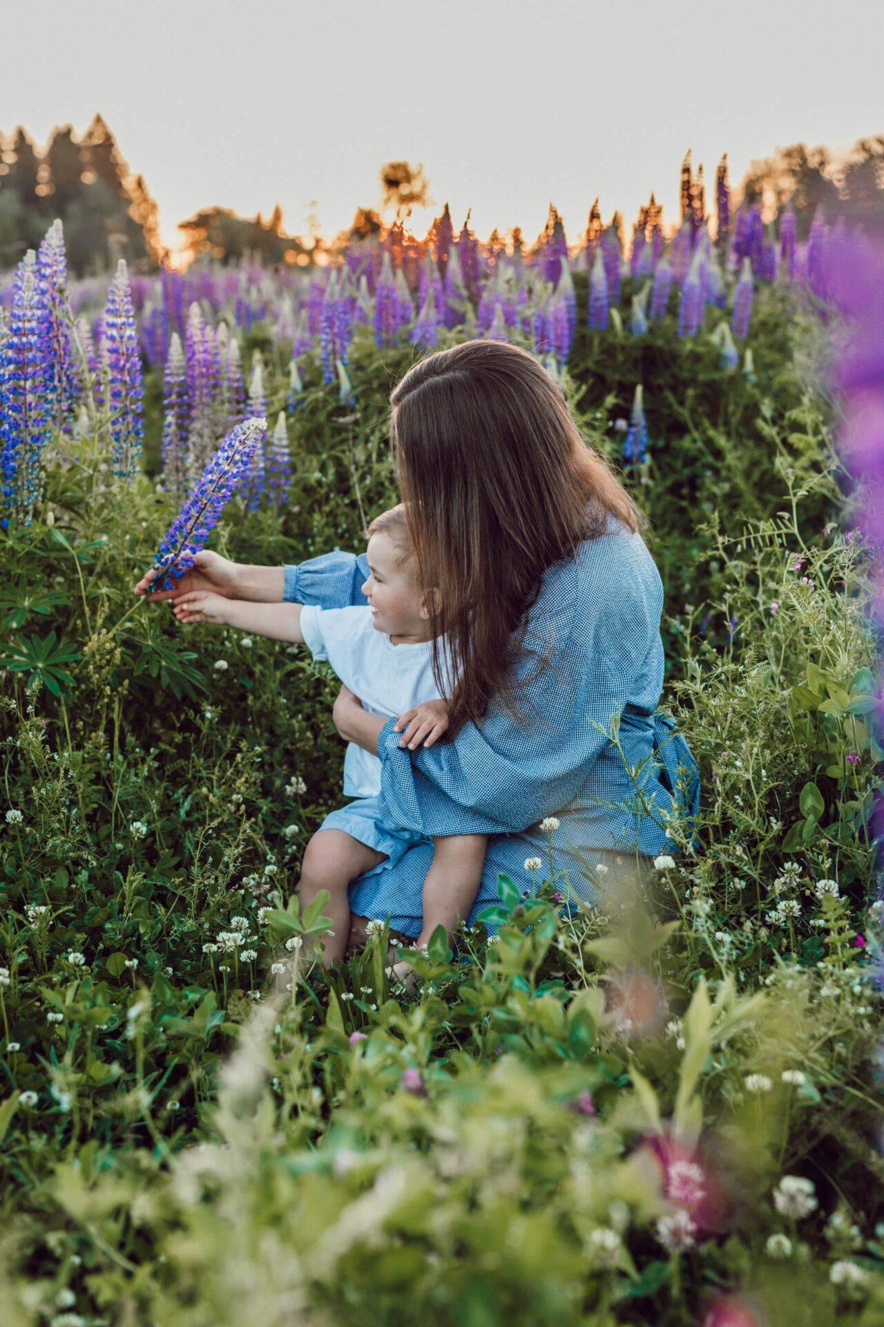 Gastouder samen met kindje tussen de bloemen de wereld aan het ontdekken