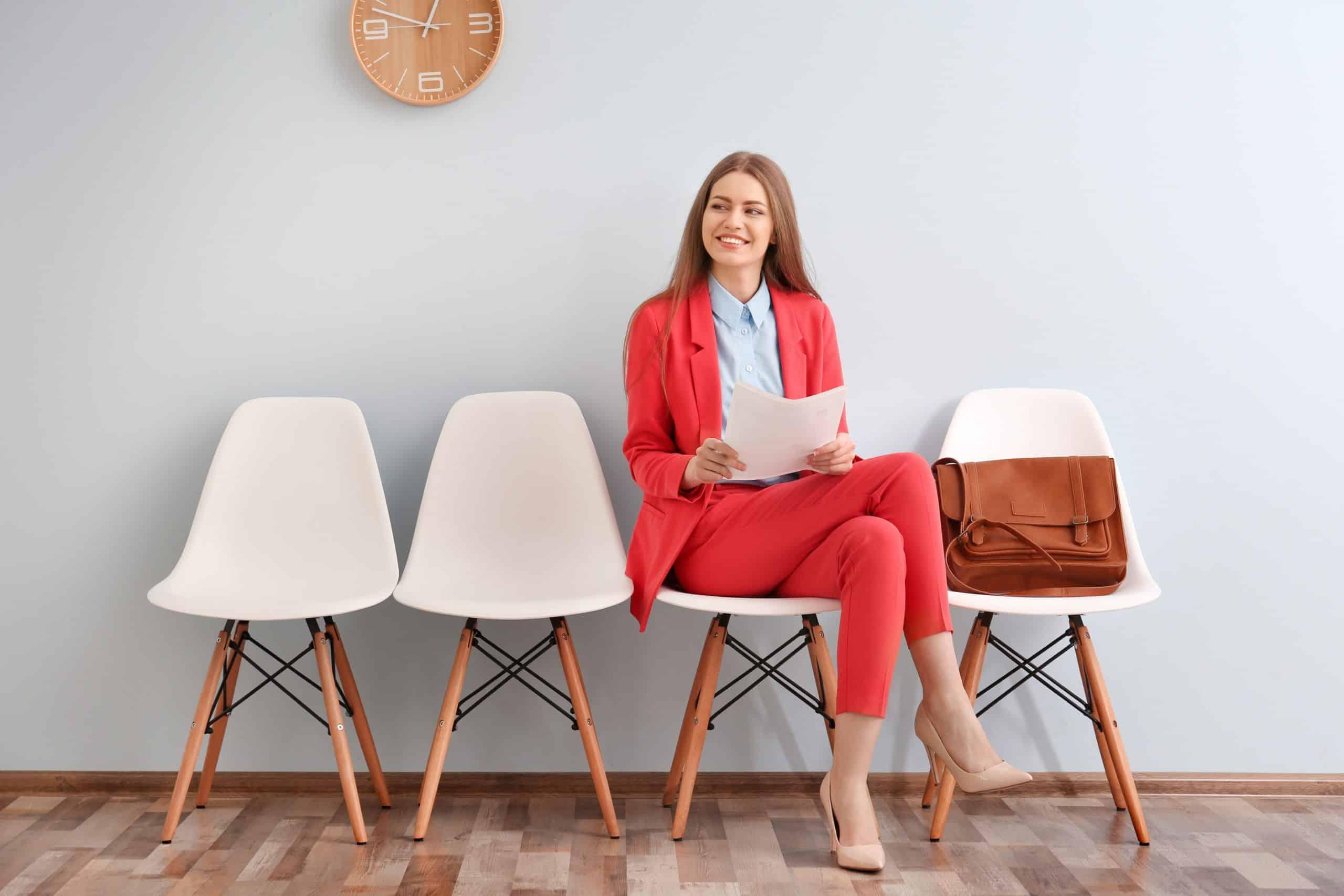 oppas in roze pak zit te wachten op stoel terwijl ze verzekering papieren bekijkt
