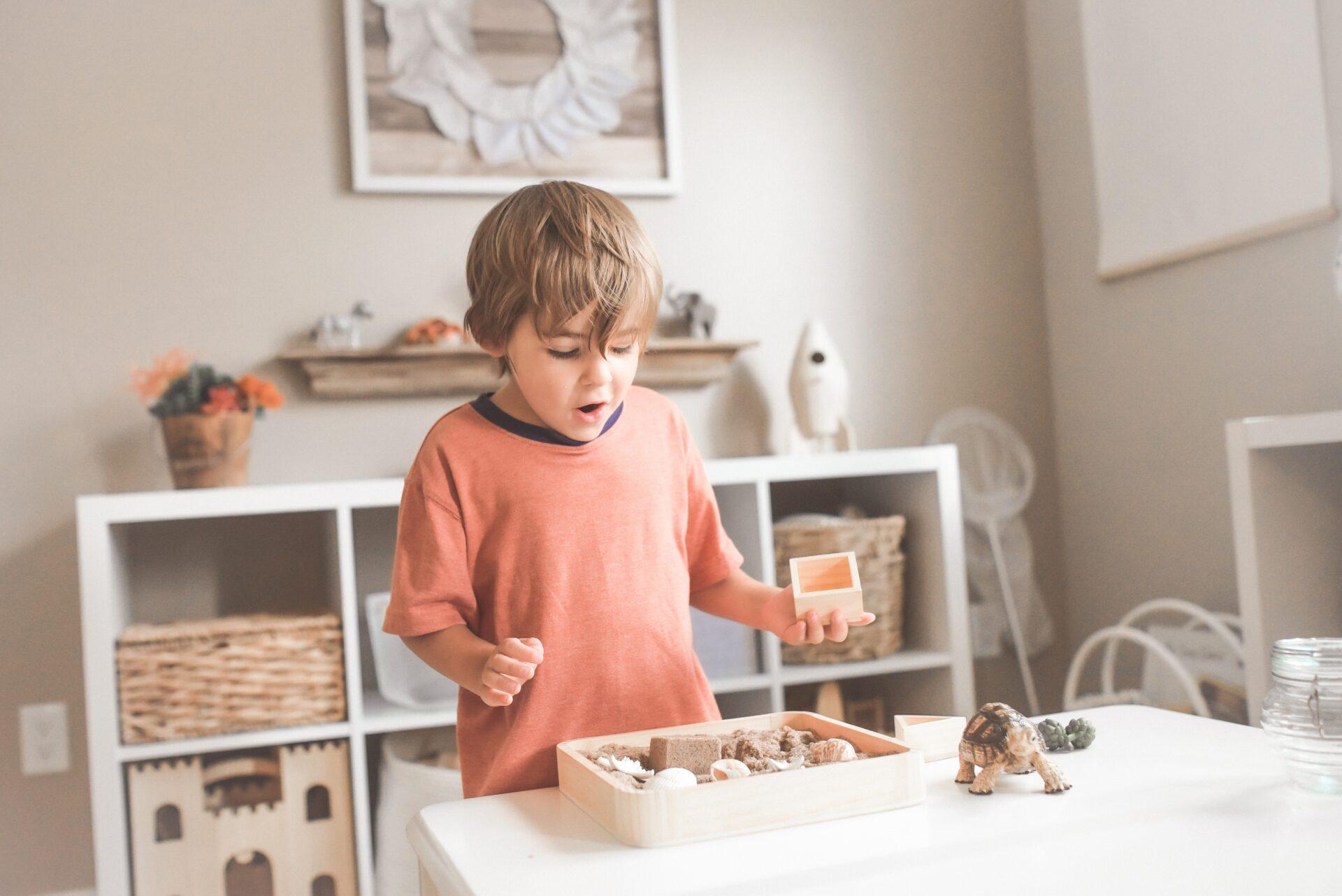 Jongetje kijkt heel blij naar een doos met blokken terwijl hij alleen aan het spelen is
