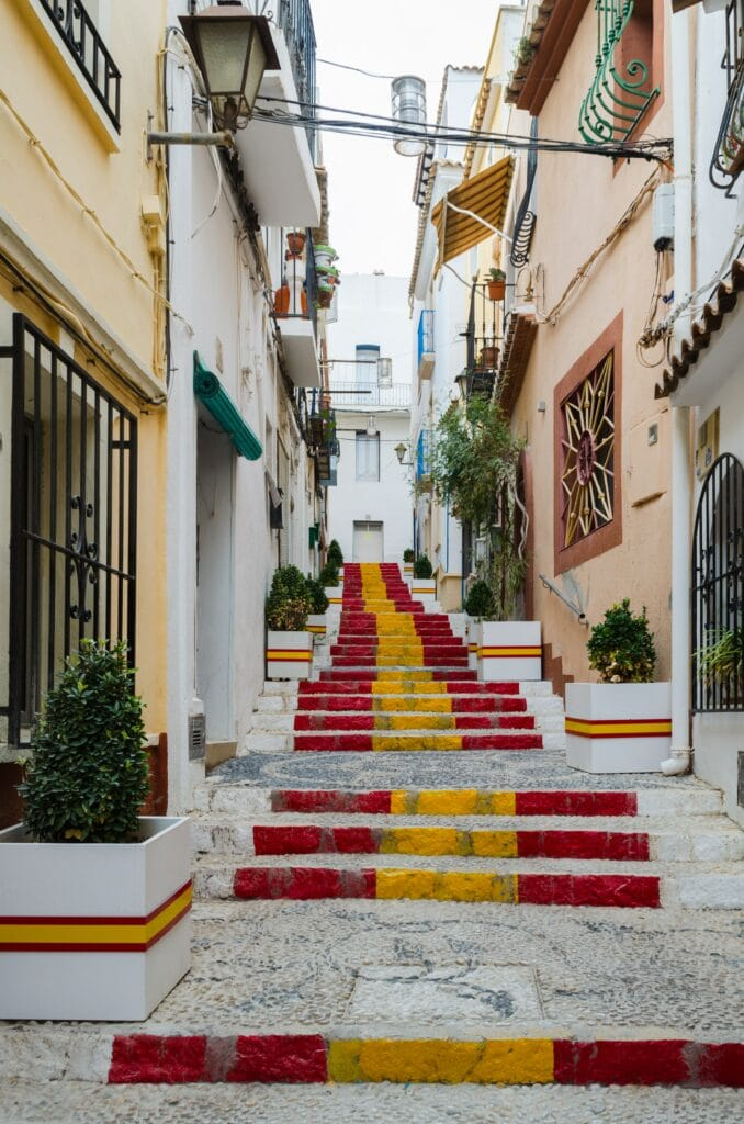 Stairs in the middle of a street with orange and yellow houses painted with flag from Spain